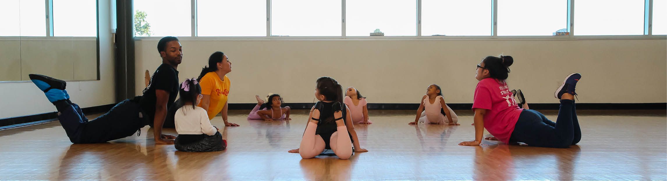 Youth Ballet participants warming up and stretching in a circle
