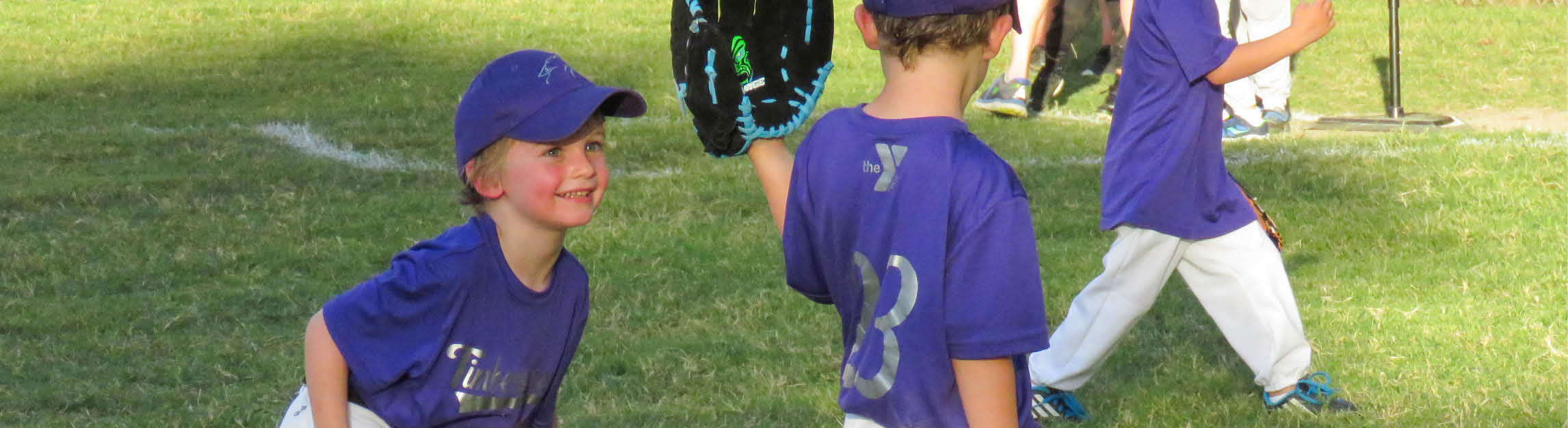 Youth Baseball participant smiling in a purple jersey and baseball cap