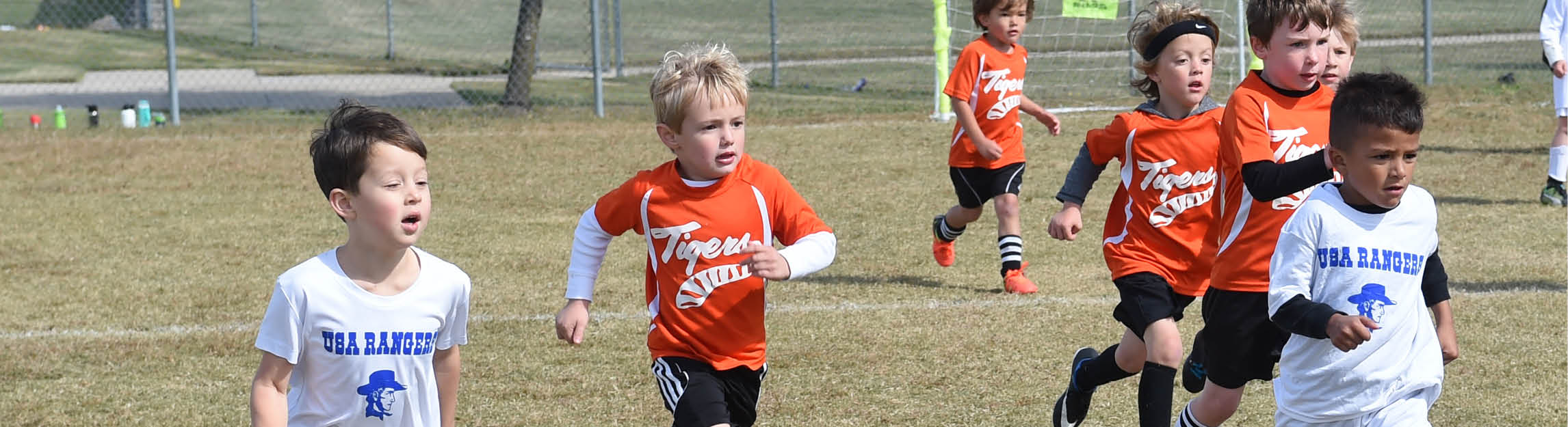 Male soccer players in white and orange jerseys running down the field