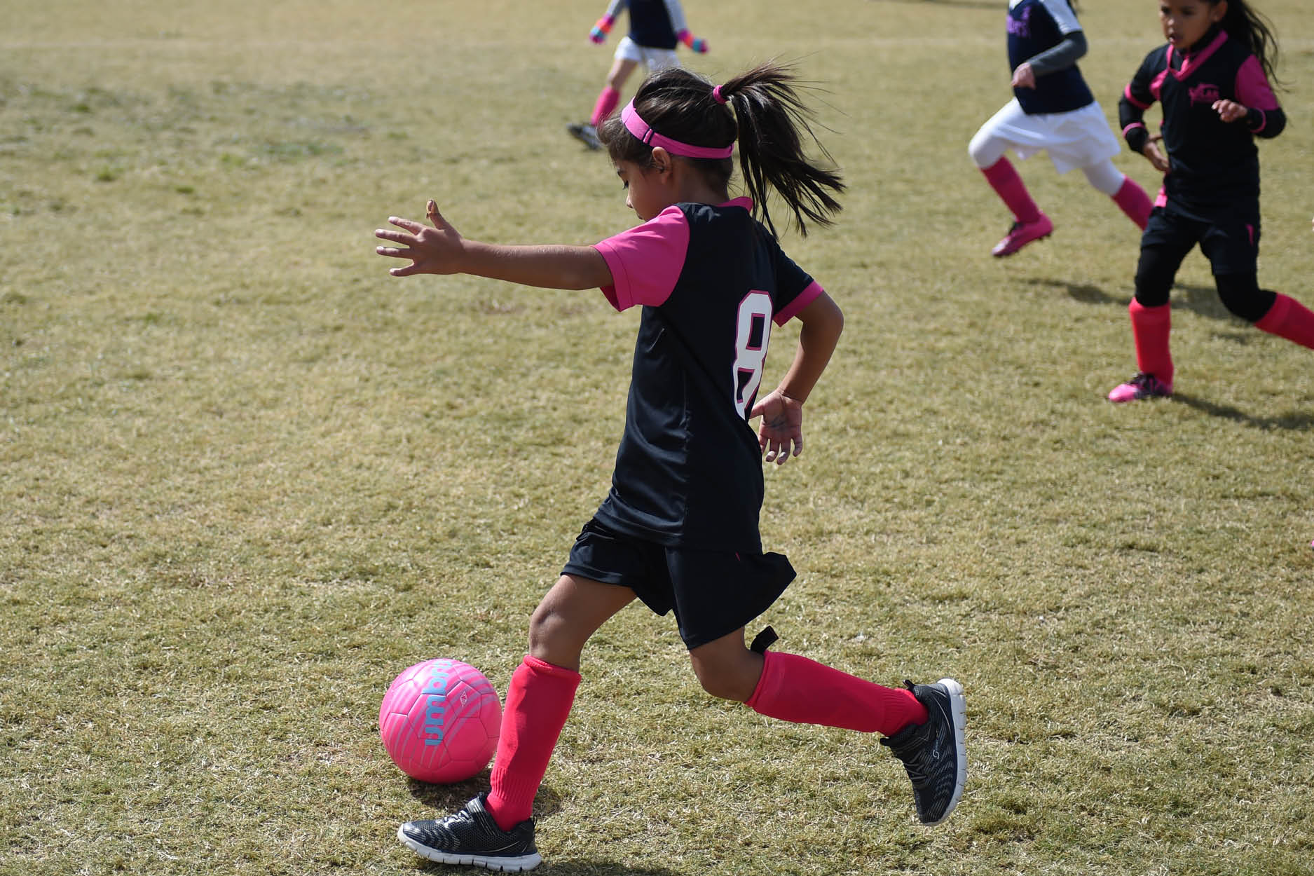 Female soccer playing in black and pink jersey kicking soccer ball