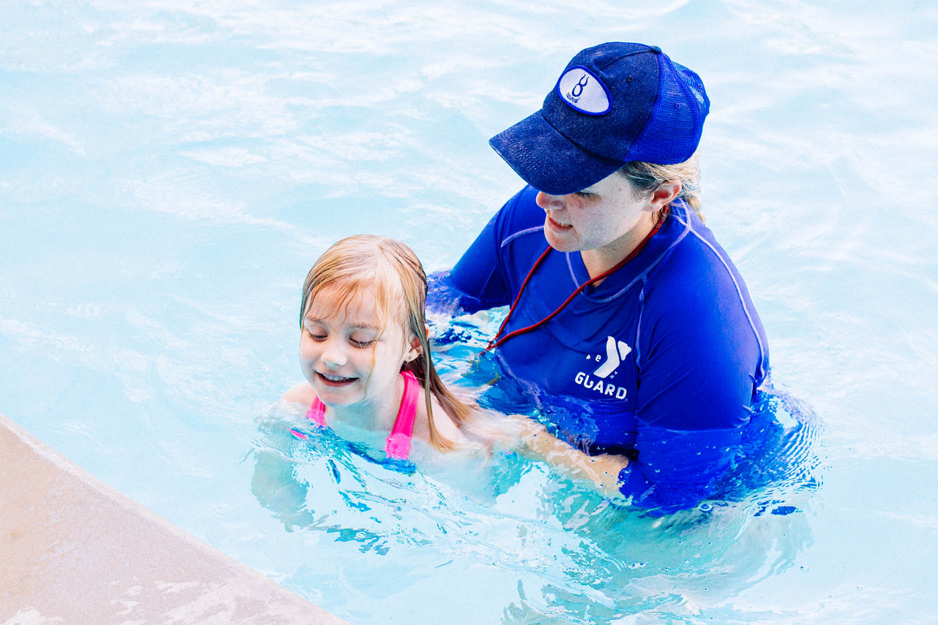 Lifeguard assisting female child during a swim lesson