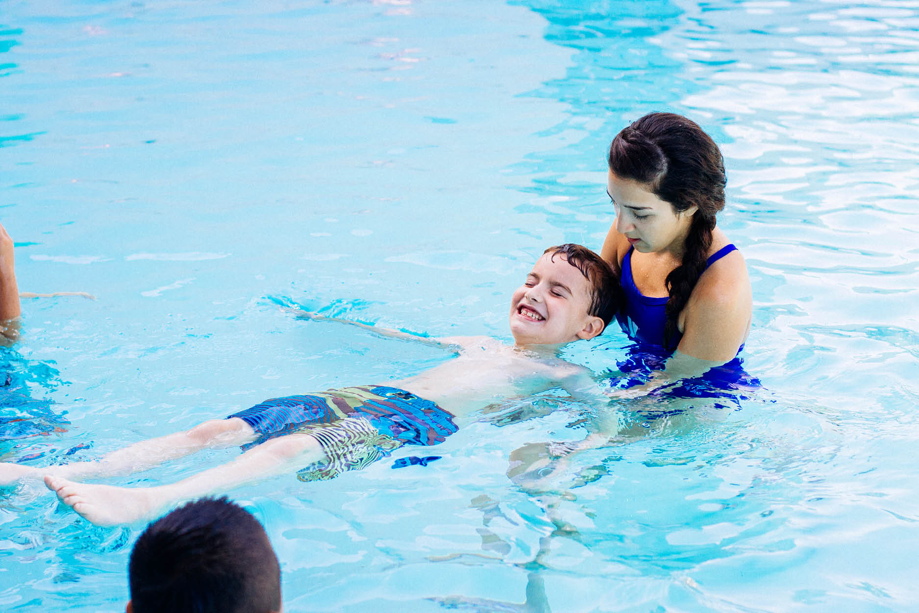 Lifeguard assisting male child with back floating during swim lesson