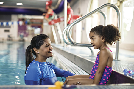 Young girl talking to a swim instructor in the pool