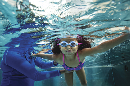 A young girl swimming with her head underwater