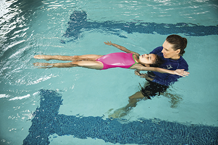 A young girl floating on her back assisted by an instructor