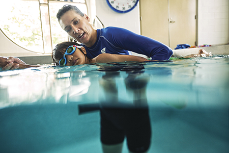 An instructor assisting a swim student on proper form while swimming