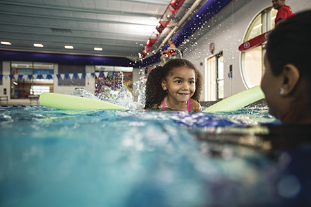 Young girl swimming assisted by instructor and a pool noodle