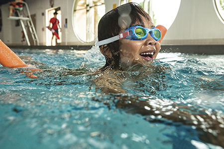 A young girl wearing goggles swimming in an indoor pool