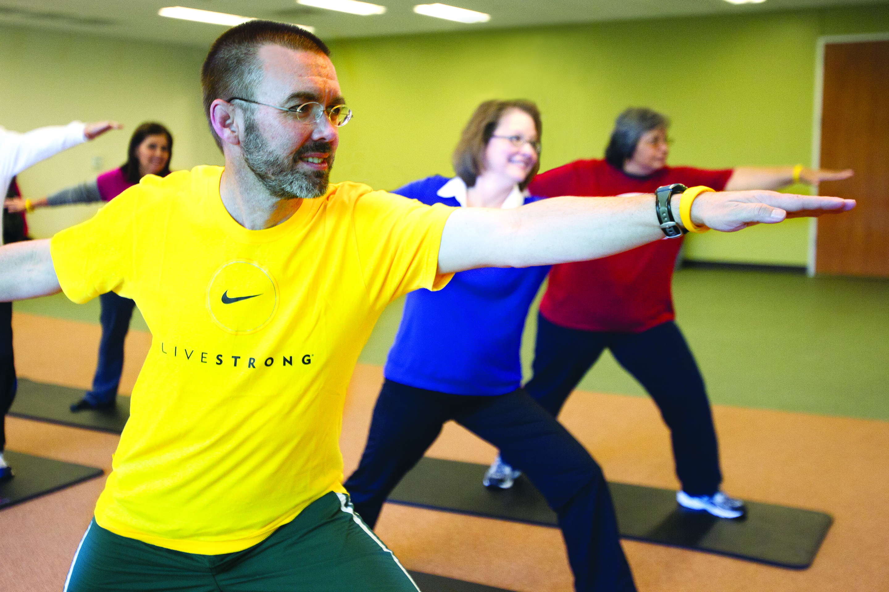 A group of adults doing yoga, one in a bright yellow LIVESTRONG shirt