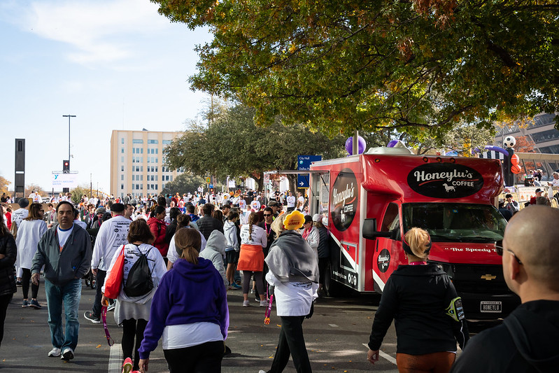 A large group of people waiting in line at a food truck