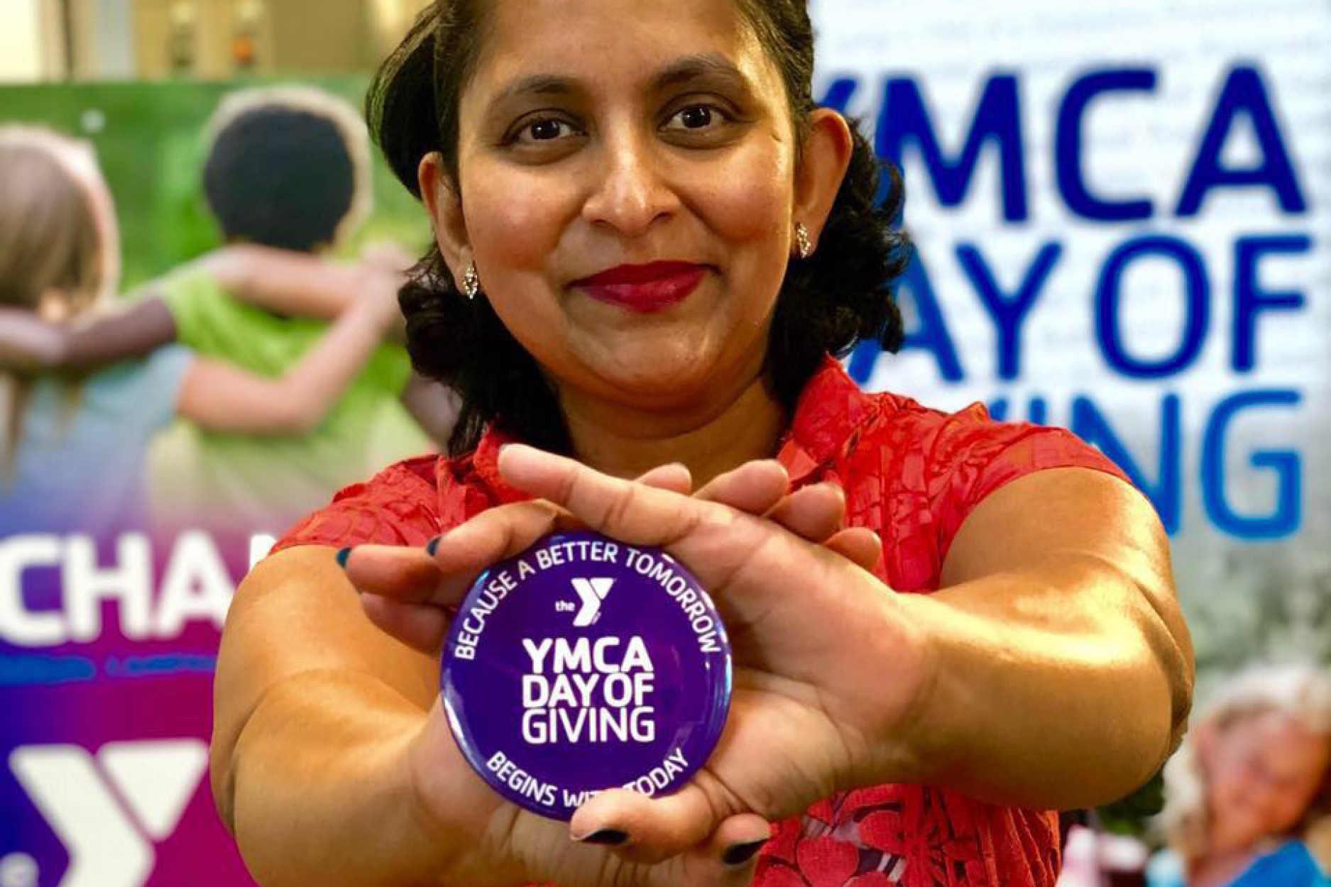 "A smiling woman holding a purple button that says ""YMCA Day of Giving"""