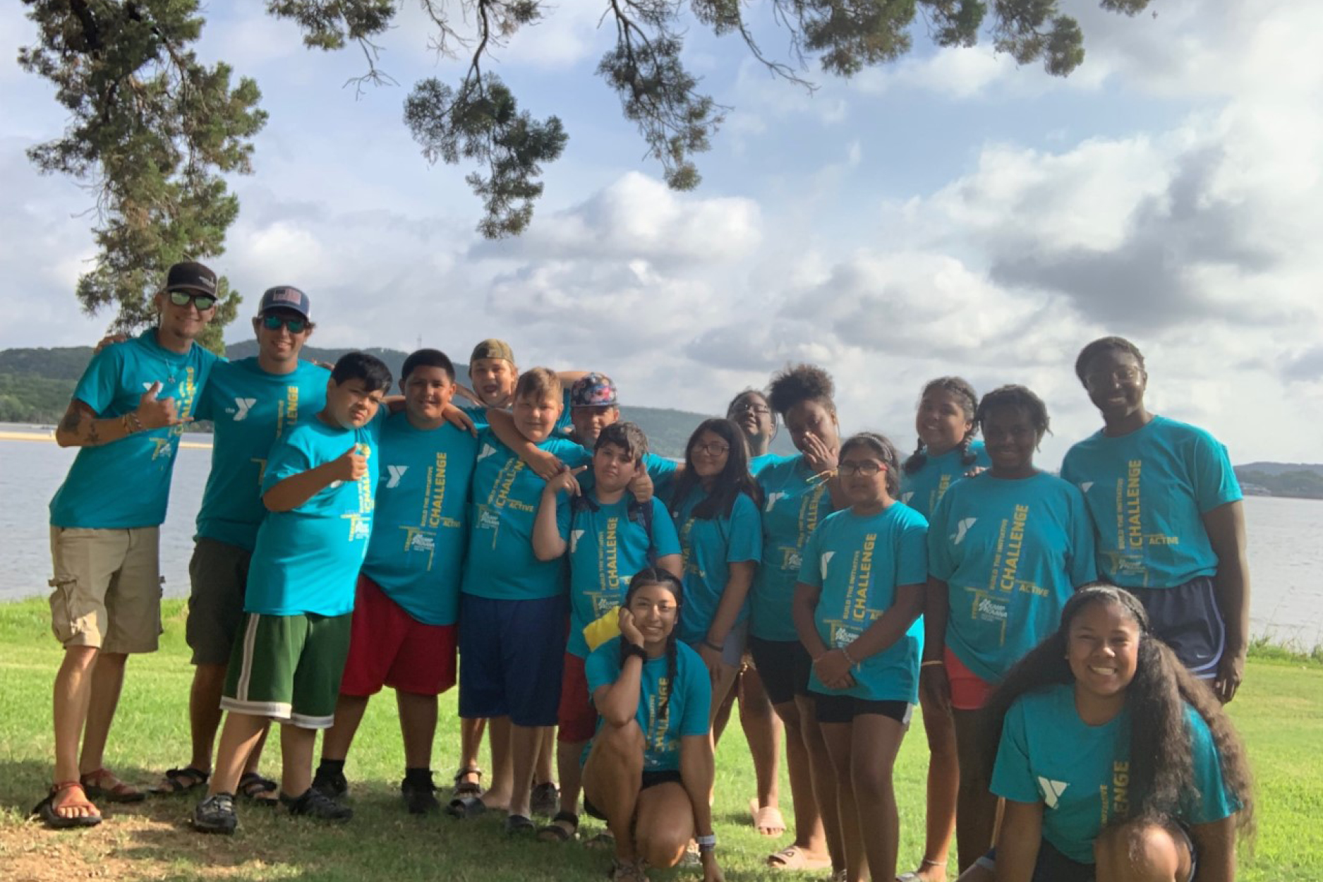 Kamp K'aana campers smiling for a photo in front of Possum Kingdom lake