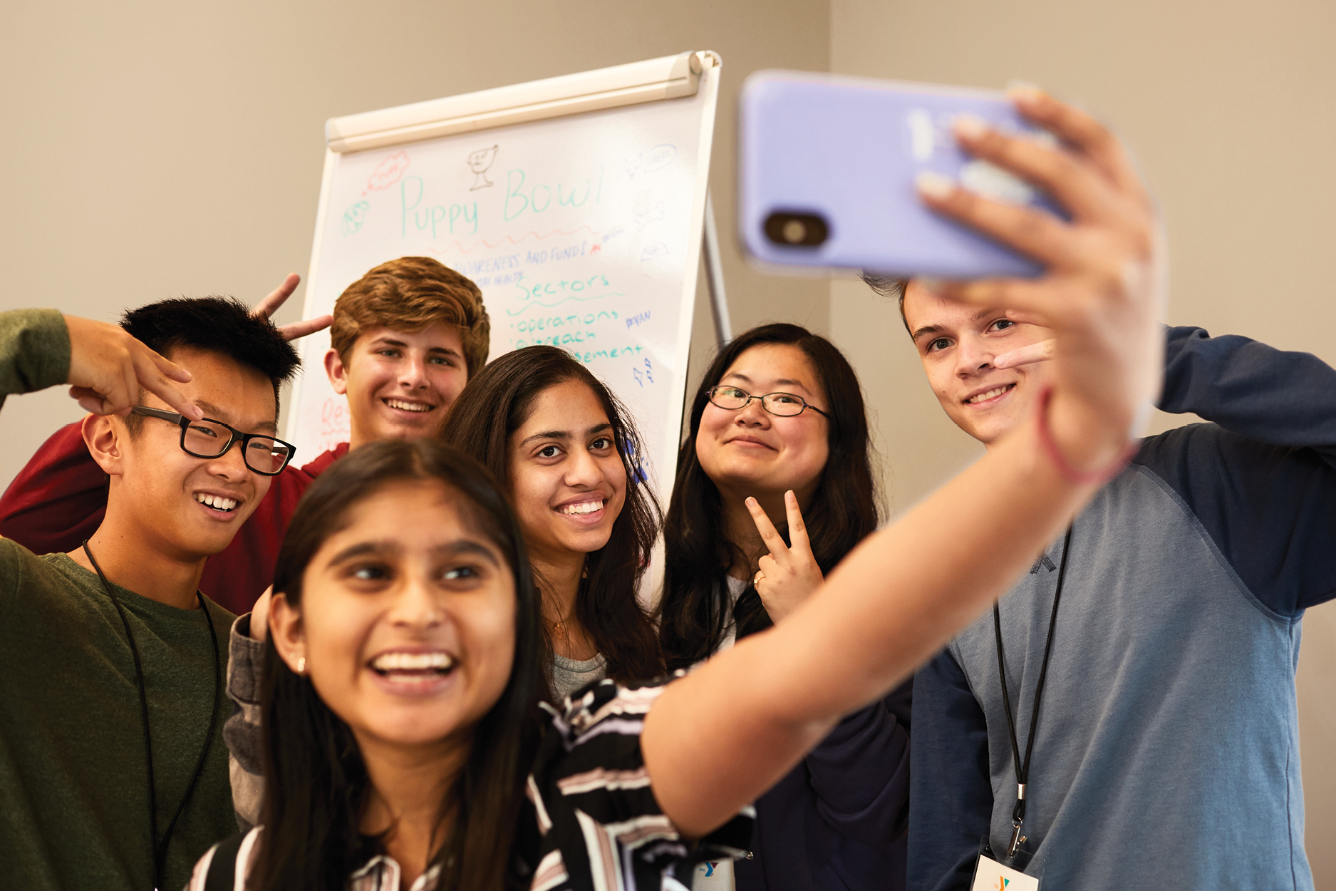 A group of middle school students smiling and posing for a selfie