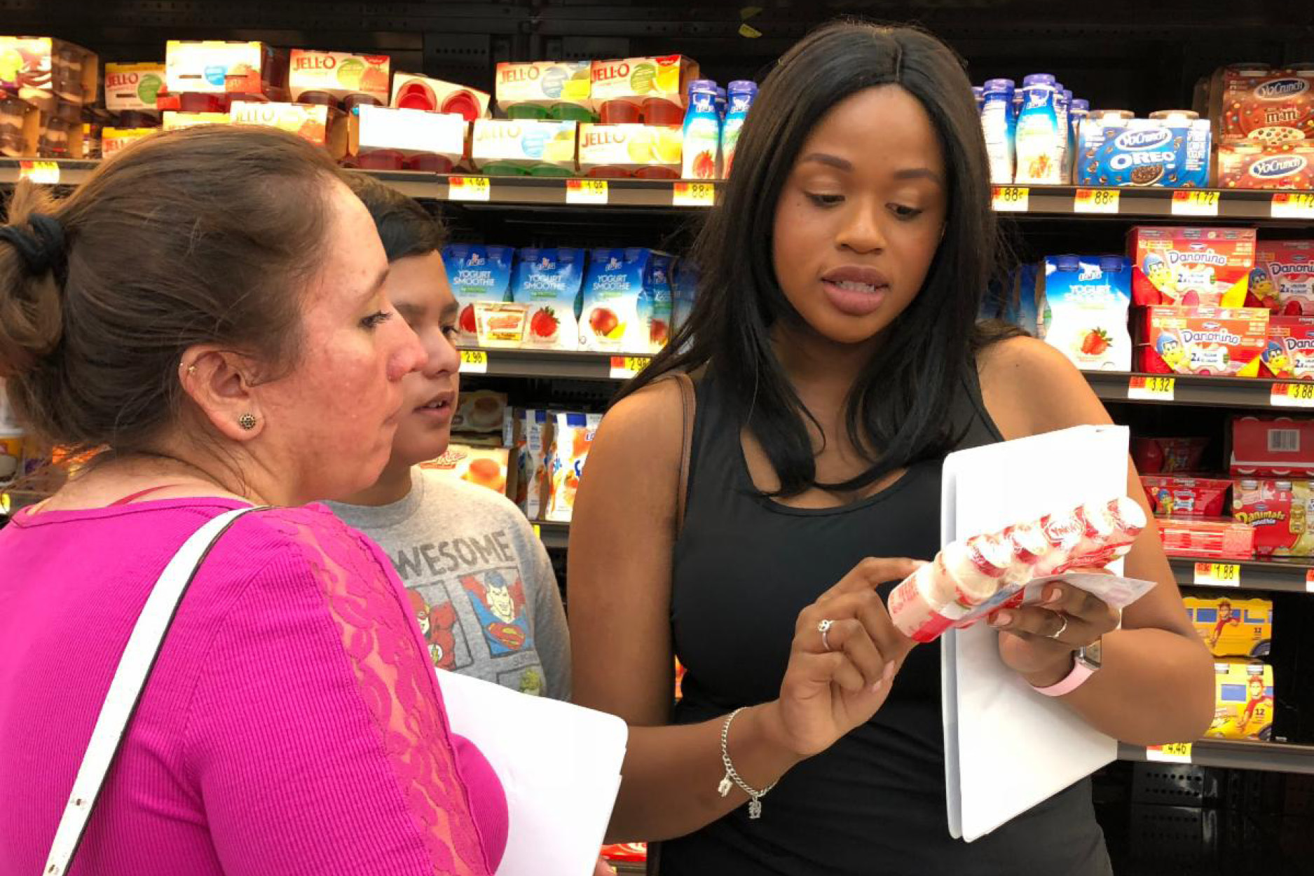 A healthy lifestyles coach showing healthy grocery options to two program participants
