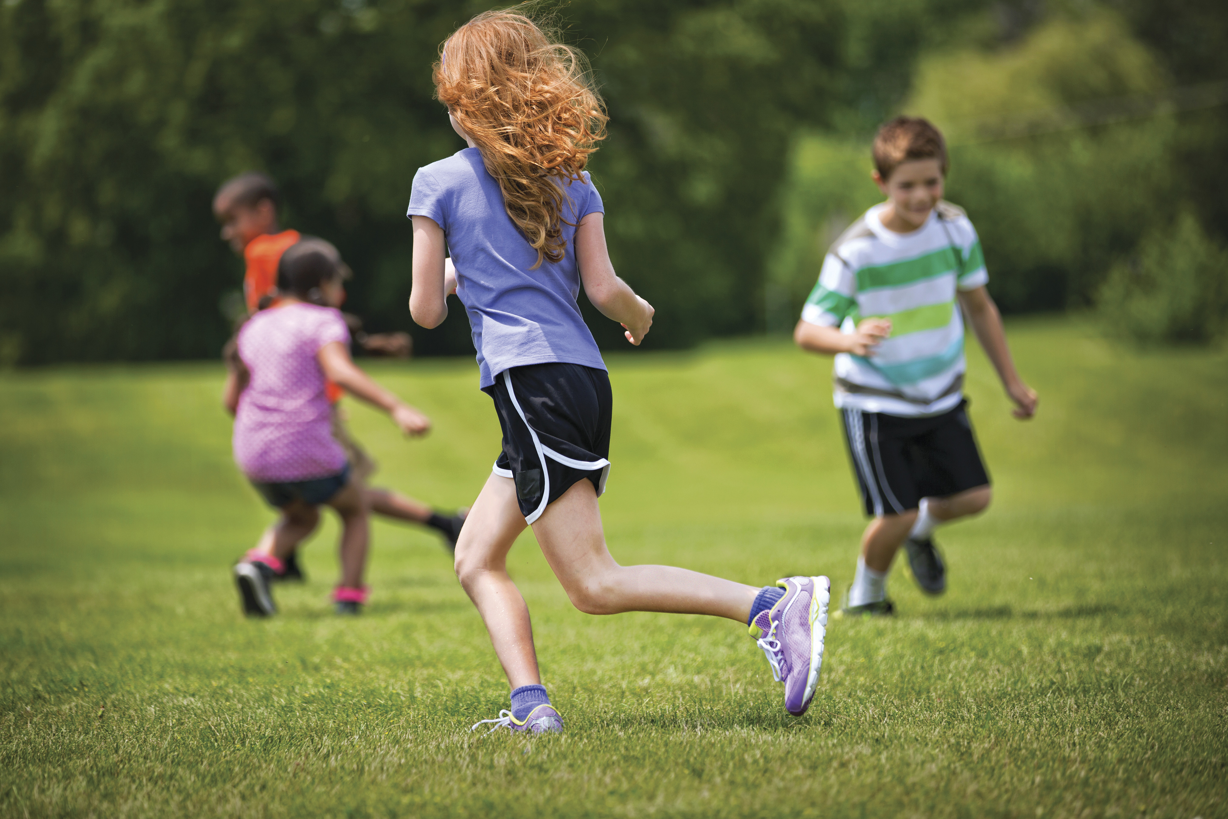 Kids running and playing in an open grassy field
