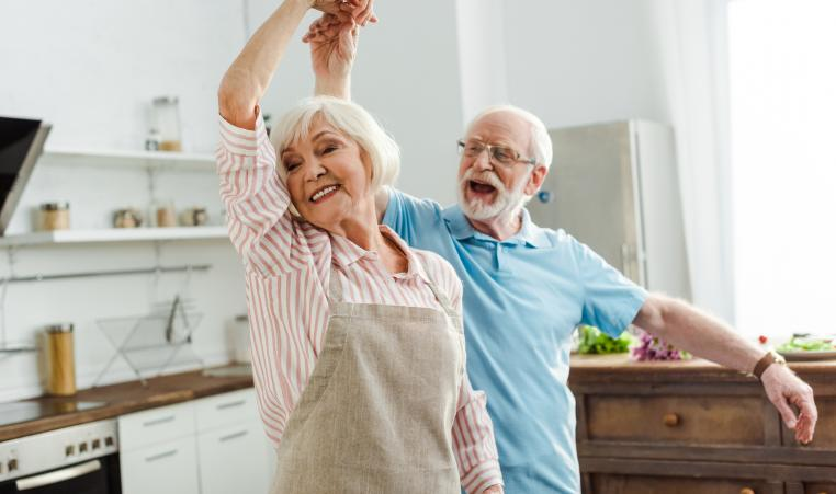 Smiling senior couple dancing in kitchen