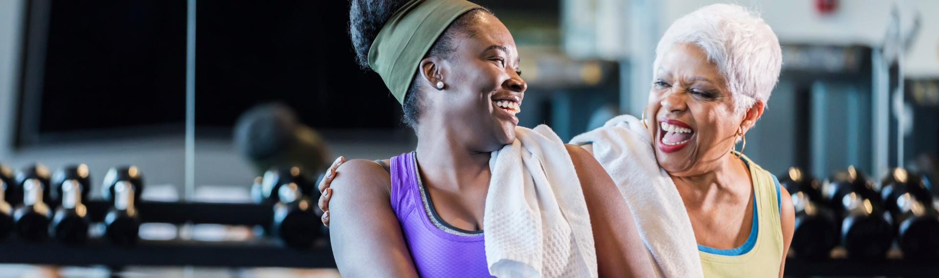 Two women in the gym looking at each other and laughing.